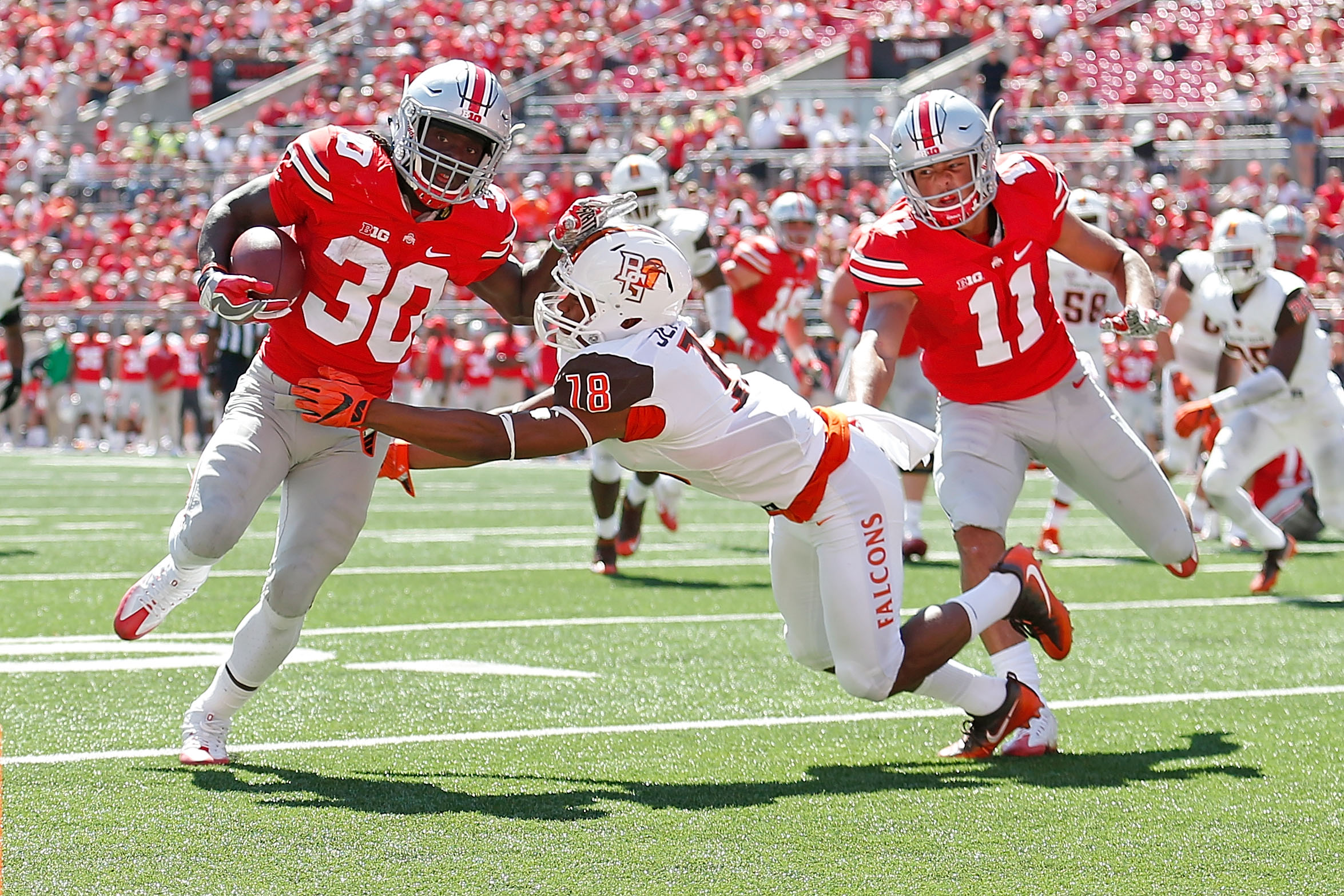 COLUMBUS, OH - SEPTEMBER 3:  Demario McCall #30 of the Ohio State Buckeyes stiff arms Cameron Jefferies #18 of the Bowling Green Falcons while carrying the ball during the fourth quarter on September 3, 2016 at Ohio Stadium in Columbus, Ohio. Ohio State defeated Bowling Green 77-10. (Photo by Kirk Irwin/Getty Images)