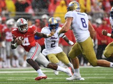 COLUMBUS, OH - SEPTEMBER 10:  Curtis Samuel #4 of the Ohio State Buckeyes eludes the defense of Jesse Brubaker #8 of the Tulsa Hurricane as he picks up 18 yards in the third quarter at Ohio Stadium on September 10, 2016 in Columbus, Ohio. Ohio State defeated Tulsa 48-3.  (Photo by Jamie Sabau/Getty Images)
