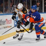 UNIONDALE, NY - JANUARY 27:  Calvin de Haan #44 of the New York Islanders checks Jordan Caron #38 of the Boston Bruins in an NHL hockey game at Nassau Veterans Memorial Coliseum on January 27, 2014 in Uniondale, New York.  (Photo by Paul Bereswill/Getty Images)