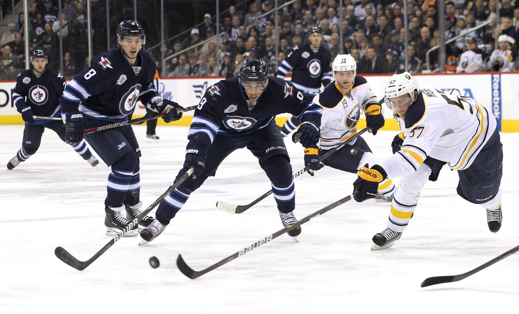 WINNIPEG, CANADA - MARCH 5: Evander Kane #9 of the Winnipeg Jets battles with Tyler Myers #57 of the Buffalo Sabres for the puck in NHL action at the MTS Centre on March 5, 2012 in Winnipeg, Manitoba, Canada. (Photo by Marianne Helm/Getty Images)