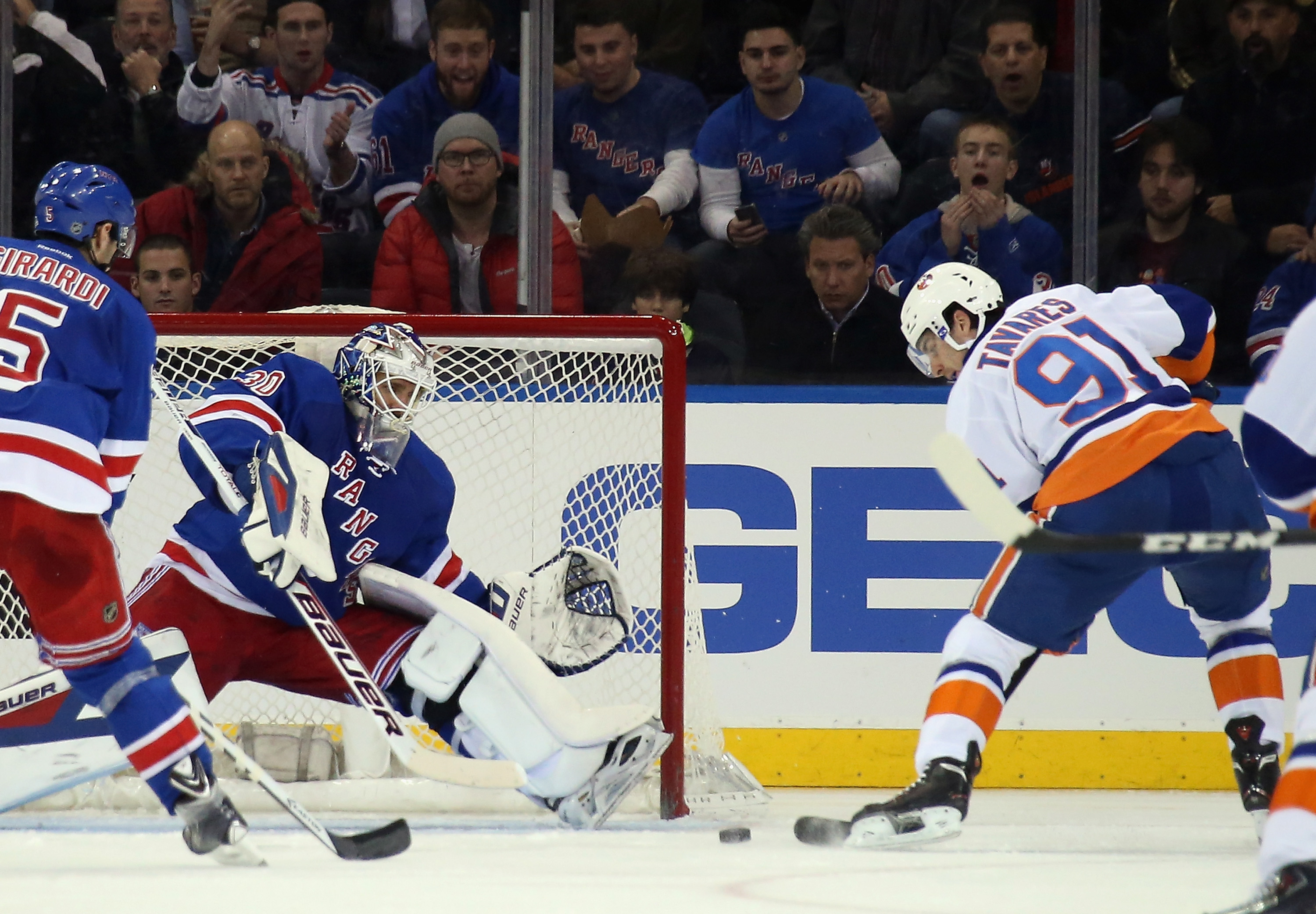NEW YORK, NY - DECEMBER 20: Henrik Lundqvist #30 of the New York Rangers moves across to stop a shot by John Tavares #91 of the New York Islanders during the second period at Madison Square Garden on December 20, 2013 in New York City.  (Photo by Bruce Bennett/Getty Images)