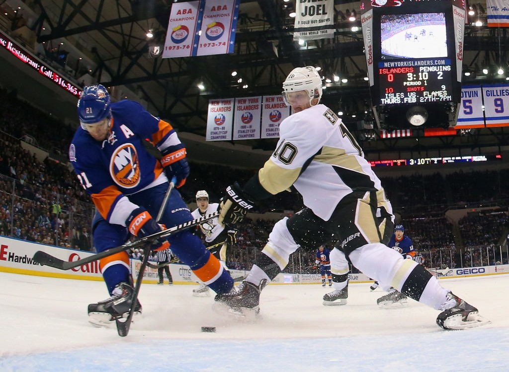 UNIONDALE, NY - JANUARY 16: Christian Ehrhoff #10 of the Pittsburgh Penguins checks Kyle Okposo #21 of the New York Islanders at the Nassau Veterans Memorial Coliseum on January 16, 2015 in Uniondale, New York.  (Photo by Bruce Bennett/Getty Images)