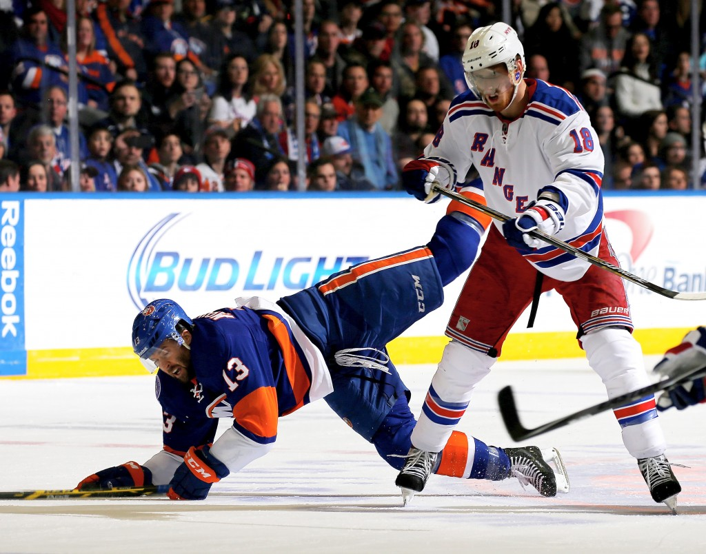 UNIONDALE, NY - FEBRUARY 16:  Colin McDonald #13 of the New York Islanders falls as he collides with Marc Staal #18 of the New York Rangers in the second period on February 16, 2015 at the Nassau Veterans Memorial Coliseum in Uniondale,New York.  (Photo by Elsa/Getty Images)