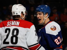 UNIONDALE, NY - FEBRUARY 28:  Anders Lee #27 of the New York Islanders speaks with Alexander Semin #28 of the Carolina Hurricanes as Lee took a hooking penalty and Semin a penalty for embellishment during the third period at the Nassau Veterans Memorial Coliseum on February 28, 2015 in Uniondale, New York.  Embellishment  (Photo by Bruce Bennett/Getty Images)