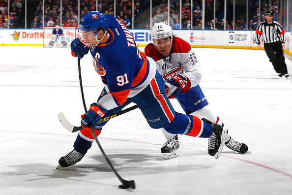 UNIONDALE, NY - MARCH 14: John Tavares #91 of the New York Islanders takes a shot on goal under pressure from P.A. Parenteau #15 of the Montreal Canadiens at Nassau Veterans Memorial Coliseum on March 14, 2015 in Uniondale, New York.  (Photo by Mike Stobe/NHLI via Getty Images)