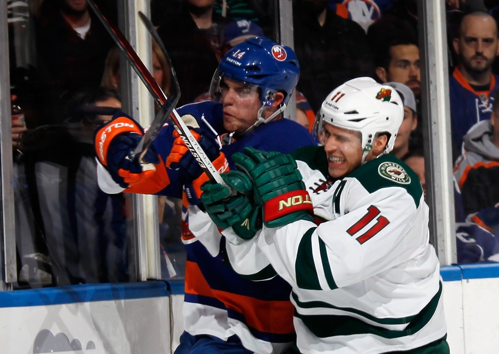 UNIONDALE, NY - MARCH 24: Thomas Hickey #14 of the New York Islanders is hit into the boards by Zach Parise #11 of the Minnesota Wild during the first period at the Nassau Veterans Memorial Coliseum on March 24, 2015 in Uniondale, New York.  (Photo by Bruce Bennett/Getty Images)