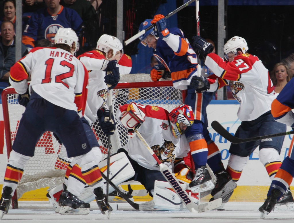 UNIONDALE, NY - APRIL 01: Casey Cizikas #53 of the New York Islanders is hit into Scott Clemmensen #30 of the Florida Panthers at the Nassau Veterans Memorial Coliseum on April 1, 2014 in Uniondale, New York.  The Islanders defeated the Panthers 4-2. (Photo by Bruce Bennett/Getty Images)