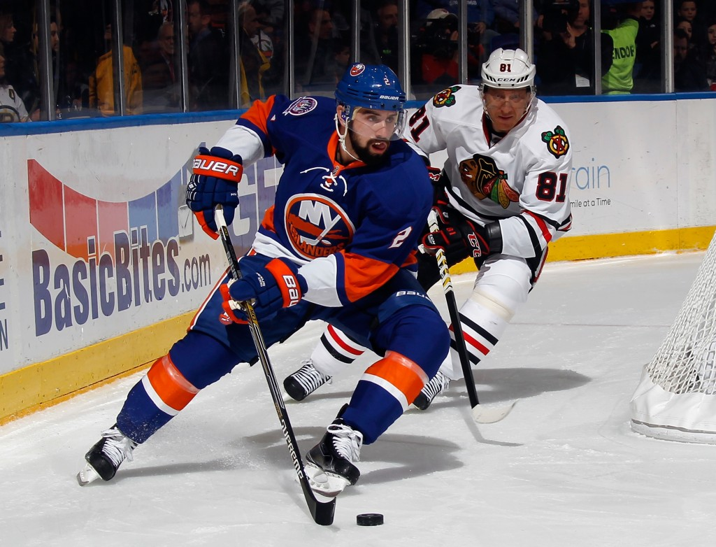 UNIONDALE, NY - DECEMBER 13: Nick Leddy #2 of the New York Islanders moves the puck past Marian Hossa #81 of the Chicago Blackhawks during the first period at the Nassau Veterans Memorial Coliseum on December 13, 2014 in Uniondale, New York.  (Photo by Bruce Bennett/Getty Images)