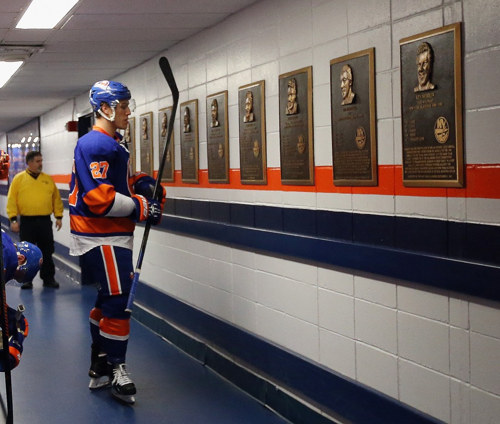 UNIONDALE, NY - APRIL 11: Anders Lee #27 of the New York Islanders looks at commemmorative player plaques prior to warmups at the Nassau Veterans Memorial Coliseum on April 11, 2015 in Uniondale, New York. This is the last regular season game to be played in the building as it stands now. The team will relocate to the Barclay's Center in the Brooklyn borough of New York City starting in the 2015-16 season.  (Photo by Bruce Bennett/Getty Images)