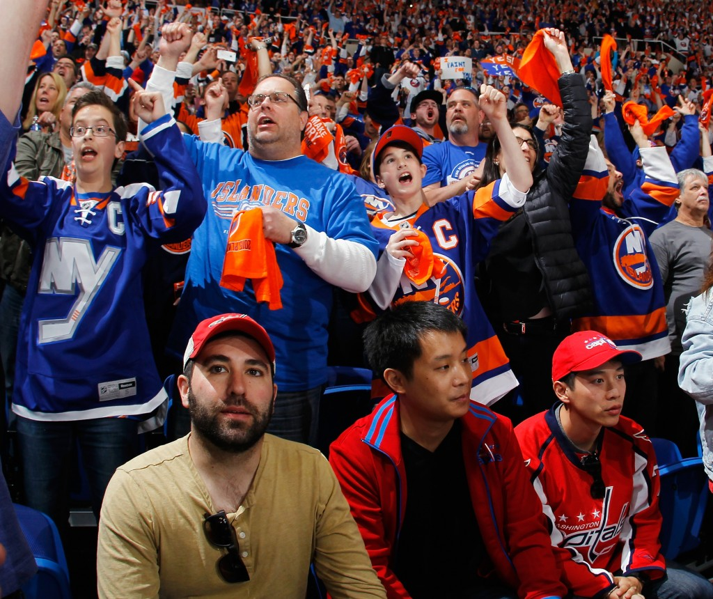 UNIONDALE, NY - APRIL 19: The New York Islanders fans celebrate a second period goal by Kyle Okposo #21 as Washington Capitals fans wait for the faceoff in Game Three of the Eastern Conference Quarterfinals during the 2015 NHL Stanley Cup Playoffs at the Nassau Veterans Memorial Coliseum on April 19, 2015 in Uniondale, New York.  (Photo by Bruce Bennett/Getty Images)