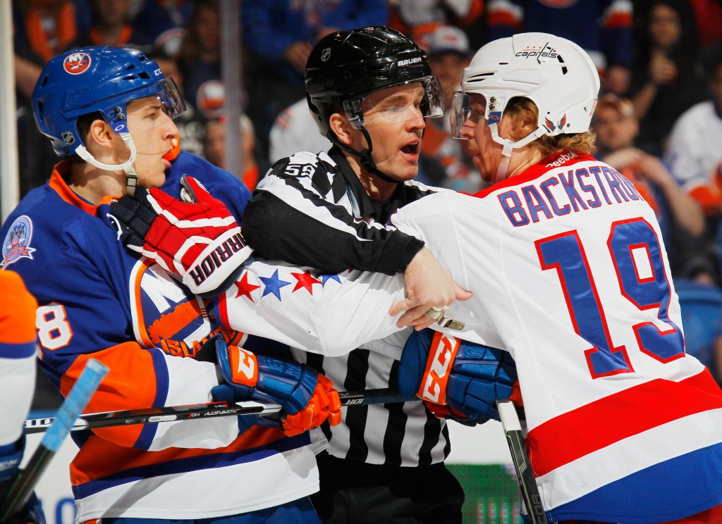 UNIONDALE, NY - APRIL 25: Ryan Strome #18 of the New York Islanders and Nicklas Backstrom #19 of the Washington Capitals exchange shoves during the first period as linesman Steve Barton #59 stands between them during the first period in Game Six of the Eastern Conference Quarterfinals during the 2015 NHL Stanley Cup Playoffs at the Nassau Veterans Memorial Coliseum on April 25, 2015 in Uniondale, New York.  (Photo by Bruce Bennett/Getty Images)