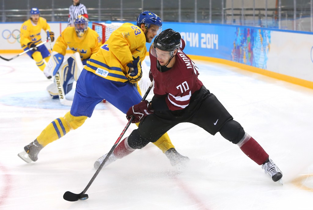 SOCHI, RUSSIA - FEBRUARY 15: Miks Indrasis #70 of Latvia handles the puck against Alexander Edler #23 of Sweden in the first period during the Men's Ice Hockey Preliminary Round Group C game on day eight of the Sochi 2014 Winter Olympics at Shayba Arena on February 15, 2014 in Sochi, Russia. (Photo by Martin Rose/Getty Images)