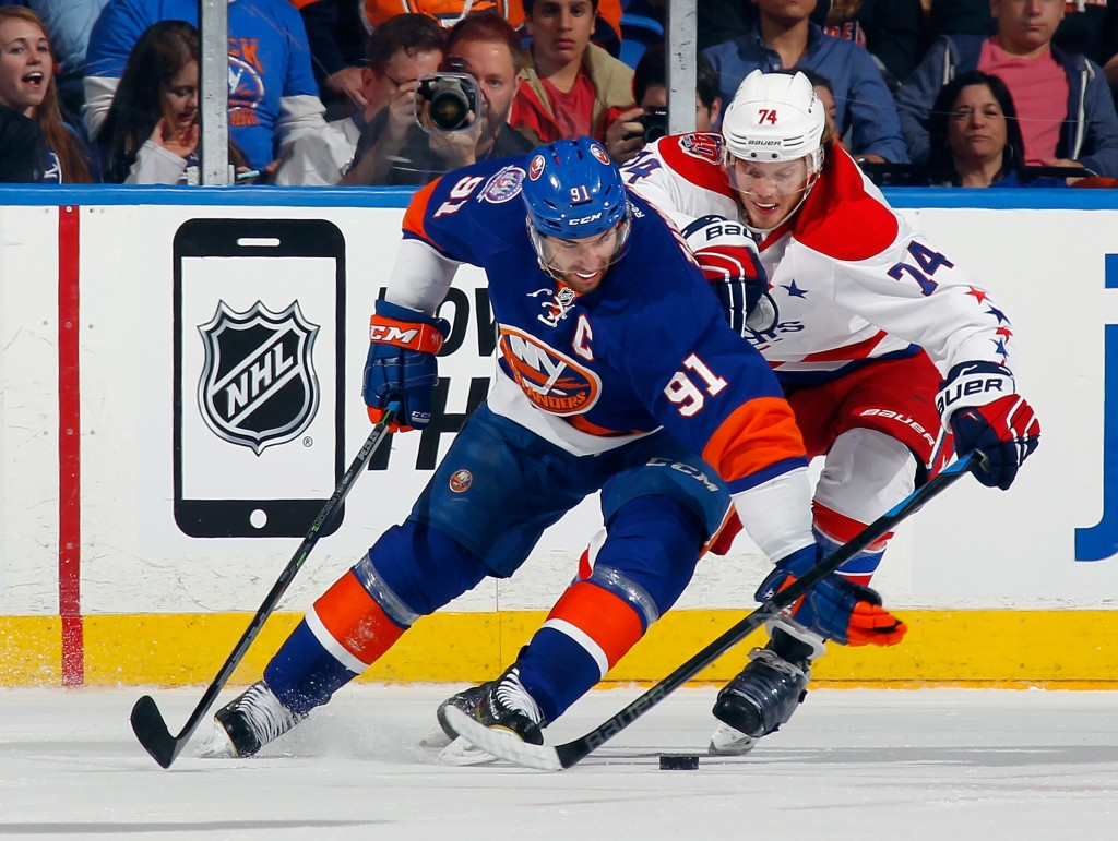 UNIONDALE, NY - APRIL 25: John Tavares #91 of the New York Islanders attempts to move the puck around John Carlson #74 of the Washington Capitals during the second period in Game Six of the Eastern Conference Quarterfinals during the 2015 NHL Stanley Cup Playoffs at the Nassau Veterans Memorial Coliseum on April 25, 2015 in Uniondale, New York.  (Photo by Bruce Bennett/Getty Images)