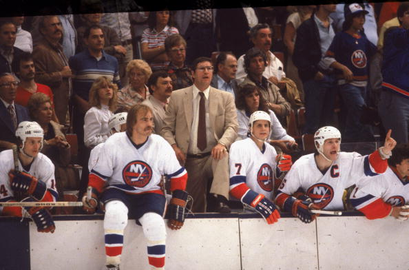 New York Islanders head coach Al Arbour (center, in suit) stands on the bench to watch a home game at Nassau Coliseum, Uniondale, Long Island, New York, May 1982. Arbour is flanked by Islanders players (from left) Bob Bourne, Bob Nystrom, Stefan Persson, Denis Potvin, and Roland Melanson. (Photo by Bruce Bennett Studios/Getty Images)