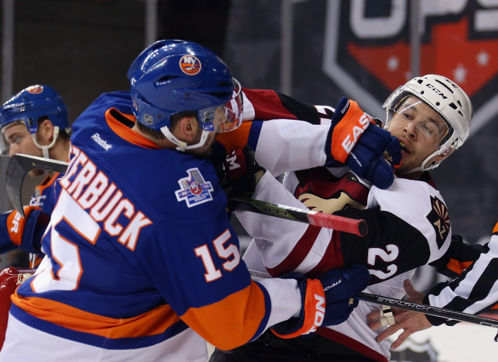 NEW YORK, NY - NOVEMBER 16: Cal Clutterbuck #15 of the New York Islanders and Craig Cunningham #22 of the Arizona Coyotes battle during the first period at the Barclays Center on November 16, 2015 in the Brooklyn borough of New York City.  (Photo by Bruce Bennett/Getty Images)