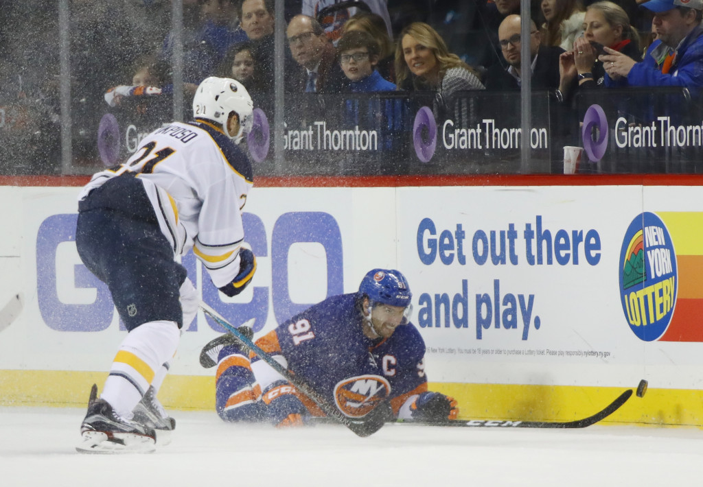 NEW YORK, NY - DECEMBER 23: John Tavares #91 of the New York Islanders pushes the puck away from Kyle Okposo #21 of the Buffalo Sabres during the first period at the Barclays Center on December 23, 2016 in the Brooklyn borough of New York City.  (Photo by Bruce Bennett/Getty Images)
