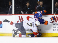 NEW YORK, NY - JANUARY 11: Colton Sceviour #7 of the Florida Panthers hits Adam Pelech #50 of the New York Islanders into the boards during the first period at the Barclays Center on January 11, 2017 in the Brooklyn borough of New York City.  (Photo by Bruce Bennett/Getty Images)