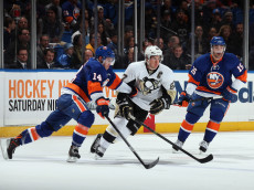 UNIONDALE, NY - DECEMBER 03: Sidney Crosby #87 of the Pittsburgh Penguins is checked by Thomas Hickey #14 and Cal Clutterbuck #15 of the New York Islanders during the first period at the Nassau Veterans Memorial Coliseum on December 3, 2013 in Uniondale, New York.  (Photo by Bruce Bennett/Getty Images)