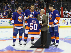 NEW YORK, NY - JANUARY 11: (l-R) Cal Clutterbuck #15, Andrew Ladd #16, Jiggs McDonald and John Tavares #91 of the New York Islanders take part in a ceremony honoring McDonald prior to the game against the Florida Panthers at the Barclays Center on January 11, 2017 in the Brooklyn borough of New York City.  (Photo by Bruce Bennett/Getty Images)