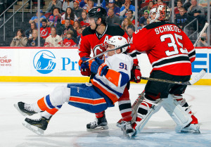 NEWARK, NJ - FEBRUARY 18: John Tavares #91 of the New York Islanders falls to the ice in front of Adam Henrique #14 and Cory Schneider #35 of the New Jersey Devils during the third period on February 18, 2017 at Prudential Center in Newark, New Jersey. (Photo by Jim McIsaac/Getty Images)