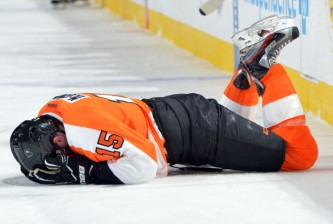 PHILADELPHIA, PA - FEBRUARY 09: Tye McGinn #15 of the Philadelphia Flyers lays on the ice after getting injured by a hit during the game against the Carolina Hurricanes at the Wells Fargo Center on February 9, 2013 in Philadelphia, Pennsylvania. (Photo by Drew Hallowell/Getty Images)