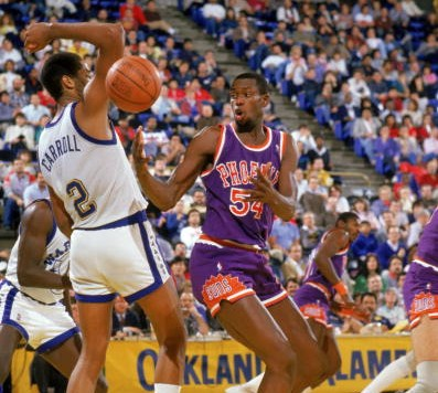 OAKLAND, CA - 1988:  Ed Pickney #54 of the Phoenix Suns battles for a loose ball with Joe Barry Carroll #2 of the Golden State Warriors during a 1988 season NBA game at the Oakland Coliseum in Oakland, California. (Photo by Otto Greule Jr./Getty Images)