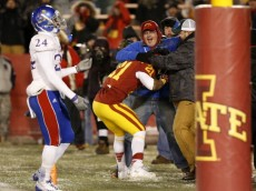 AMES, IA - NOVEMBER 23: Running back Shontrelle Johnson #21 of the Iowa State Cyclones celebrates with fans after scoring a touchdown in the second half of play as cornerback JaCorey Shepherd #24 of the Kansas Jayhawks watches on at Jack Trice Stadium on November 23, 2013 in Ames, Iowa. Iowa State defeated Kansas 34-0. (Photo by David Purdy/Getty Images)