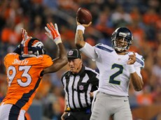 DENVER, CO - AUGUST 07:  Quarterback Terrelle Pryor #2 of the Seattle Seahawks passes under coverage by defensive end Quanterus Smith #93 of the Denver Broncos during preseason action at Sports Authority Field at Mile High on August 7, 2014 in Denver, Colorado.  (Photo by Doug Pensinger/Getty Images)