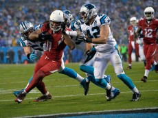 CHARLOTTE, NC - JANUARY 03:  Larry Fitzgerald #11 of the Arizona Cardinals tries to avoid the tackle of  Colin Jones #42 and  Luke Kuechly #59 of the Carolina Panthers during their NFC Wild Card Playoff game at Bank of America Stadium on January 3, 2015 in Charlotte, North Carolina.  (Photo by Grant Halverson/Getty Images)