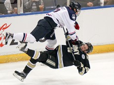 UConn's Derek Pratt (2) flattens Army's Conor Andrie (20) with a check during the UConn Huskies vs Army Black Knights men's college hockey game at the XL Center in Hartford, CT on November 10, 2015.
