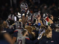 The UConn football team celebrates after their 20-17 upset win over the Houston Cougars at Pratt & Whitney Stadium at Rentschler Field in East Hartford, CT on November 21, 2015.
