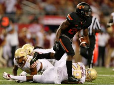 ARLINGTON, TX - AUGUST 30:  Tyreek Hill #24 of the Oklahoma State Cowboys runs with the ball as Nate Andrews #29 of the Florida State Seminoles is on the ground in the first half of the Advocare Cowboys Classic at AT&T Stadium on August 30, 2014 in Arlington, Texas.  (Photo by Tom Pennington/Getty Images)
