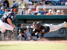LAKELAND, FL- MARCH 01:  Alen Hanson #59 of the Pittsburgh Pirates slides in safe on a RBI single in the seventh inning against Bryan Holaday #50 of the Detroit Tigers during the game at Joker Marchant Stadium on March 1, 2016 in Lakeland, Florida.  (Photo by Justin K. Aller/Getty Images)