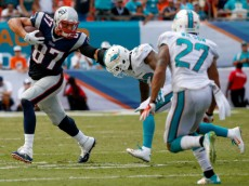 MIAMI GARDENS, FL - SEPTEMBER 07:  Rob Gronkowski #87 of the New England Patriots stiff-arms Jamar Taylor #22 of the Miami Dolphins during the second half of the game Sun Life Stadium on September 7, 2014 in Miami Gardens, Florida.  (Photo by Rob Foldy/Getty Images)