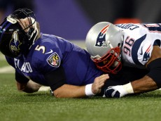 BALTIMORE, MD - DECEMBER 22: Quarterback Joe Flacco #5 of the Baltimore Ravens is hit by defensive end Andre Carter #96 of the New England Patriots in the first quarter at M&T Bank Stadium on December 22, 2013 in Baltimore, Maryland. (Photo by Patrick Smith/Getty Images)