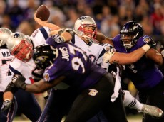 BALTIMORE, MD - DECEMBER 22: Quarterback Tom Brady #12 of the New England Patriots gets off a second half pass while being pressured by defensive end DeAngelo Tyson #93 of the Baltimore Ravens during the Patriots 41-7 win at M&T Bank Stadium on December 22, 2013 in Baltimore, Maryland.  (Photo by Rob Carr/Getty Images)