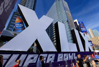 PHOENIX, AZ - JANUARY 28:  People walk past the logo for the upcoming Super Bowl XLIX between the Seattle Seahawks and New England Patriots in an NFL fan on January 28, 2015 in Phoenix, Arizona.  (Photo by Rob Carr/Getty Images)