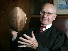 U.S. District Court Judge David S. Doty, who brokered the NFL's collective bargaining agreement with the players union in January of 1993, sits in his chambers July 7, 2005, in Minneapolis with a football signed by all the lawyers involved. (Photo by Beth Schlanker)