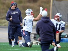 (Foxborough, MA, 12/11/15) Wide receiver #11 Julian Edelman and tight end #87 Rob Gronkowski high five as head coach Bill Belichick looks during the Patriots warm up for practice at Gillette. Friday, December 11, 2015. Staff photo by John Wilcox.