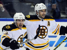Boston Bruins' Brad Marchand (63) celebrates his NHL hockey game-winning goal with teammate Patrice Bergeron (37) during the overtime session against the  Buffalo Sabres Thursday, Oct., 30, 2014, in  Buffalo , N.Y. Boston won 3-2. (AP Photo/Gary Wiepert)