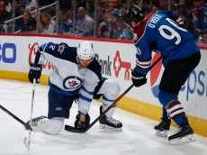 DENVER, CO - APRIL 09:  Adam Pardy #2 of the Winnipeg Jets gloves the puck against Ryan O'Reilly #90 of the Colorado Avalanche at Pepsi Center on April 9, 2015 in Denver, Colorado.  (Photo by Doug Pensinger/Getty Images)