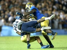 PASADENA, CA - SEPTEMBER 19:  Running back Adam Hine #28 of the BYU Cougars is tackled by linebacker Myles Jack #30 (L) and defensive back Marcus Rios #9 of the UCLA Bruins at the Rose Bowl on September 19, 2015 in Pasadena, California.  UCLA won 24-23.  (Photo by Stephen Dunn/Getty Images)