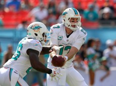 MIAMI GARDENS, FL - DECEMBER 28:  quarterback Ryan Tannehill #17 of the Miami Dolphins hands the ball to running back Lamar Miller #26 of the Miami Dolphins in the first quarter during a game against the New York Jets at Sun Life Stadium on December 28, 2014 in Miami Gardens, Florida.  (Photo by Mike Ehrmann/Getty Images)