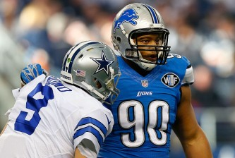ARLINGTON, TX - JANUARY 04:  Ndamukong Suh #90 of the Detroit Lions  helps Tony Romo #9 of the Dallas Cowboys to his feet during the first half of their NFC Wild Card Playoff game at AT&T Stadium on January 4, 2015 in Arlington, Texas.  (Photo by Tom Pennington/Getty Images)