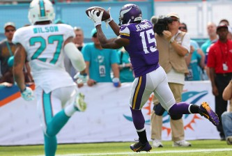MIAMI GARDENS, FL - DECEMBER 21:  Wide receiver Greg Jennings #15 of the Minnesota Vikings scores a second quarter touchdown as strong safety Jimmy Wilson #27 of the Miami Dolphins trails during a game at Sun Life Stadium on December 21, 2014 in Miami Gardens, Florida.  (Photo by Mike Ehrmann/Getty Images)