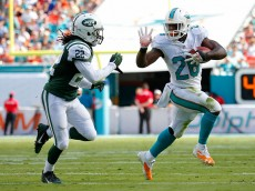 MIAMI GARDENS, FL - DECEMBER 28:  Running back Lamar Miller #26 of the Miami Dolphins tries to elude cornerback Marcus Williams #22 of the New York Jets in the second quarter during a game at Sun Life Stadium on December 28, 2014 in Miami Gardens, Florida.  (Photo by Chris Trotman/Getty Images)