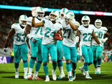 LONDON, ENGLAND - SEPTEMBER 28:  Cortland Finnegan #24 of the Miami Dolphins celebrates with teammates after returning a fumble 50 yards to score a touchdown during the NFL match between the Oakland Raiders and the Miami Dolphins at Wembley Stadium on September 28, 2014 in London, England.  (Photo by Richard Heathcote/Getty Images)