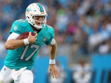 CHARLOTTE, NC - AUGUST 22:   Ryan Tannehill #17 of the Miami Dolphins runs with the ball against the Carolina Panthers during their game at Bank of America Stadium on August 22, 2015 in Charlotte, North Carolina.  (Photo by Streeter Lecka/Getty Images)