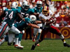 WASHINGTON - SEPTEMBER 09:  Wide receiver Santana Moss #89 of the Washington Redskins is gang tackled by Miami Dolphins defense in third quarter action at FedEx Field September 9, 2007 in Landover, Maryland.  The Redskins defeated the Dolphins 16-13.  (Photo by Win McNamee/Getty Images)