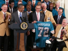 WASHINGTON, DC - AUGUST 20:  First row, U.S. President Barack Obama (2nd L) is presented with a jersey by current team owner Stephen Ross (3rd L) as members of the 1972 Miami Dolphins, head coach Don Shula (R), quarterback Bob Griese (L), running back Larry Csonka (4th L) and other members look on during an East Room event August 20, 2013 at the White House in Washington, DC. President Obama hosted the undefeated 1972 Super Bowl champions who didnt get the chance to be honored at the White House back then.  (Photo by Alex Wong/Getty Images)